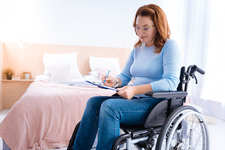 Doing job. Happy lovely smiling blond handicapped woman of middle age wearing glasses and writing while sitting in a wheelchair in a blue sweater and a bed in the background Stock Photo
