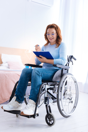 Exuberant smiling blond handicapped woman of middle age wearing glasses and writing on a sheet of paper while sitting in a wheelchair in a blue sweater