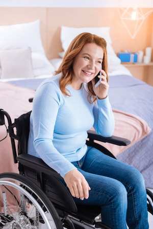 Happy blond handicapped woman of middle age smiling and talking on her phone while sitting in the wheelchair and wearing a blue sweater and a bed in the background