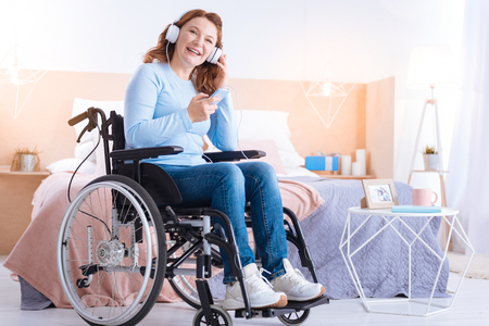 Exuberant blond handicapped woman of middle age smiling and wearing headset and holding her phone while sitting in the wheelchair in a blue sweater Stock Photo