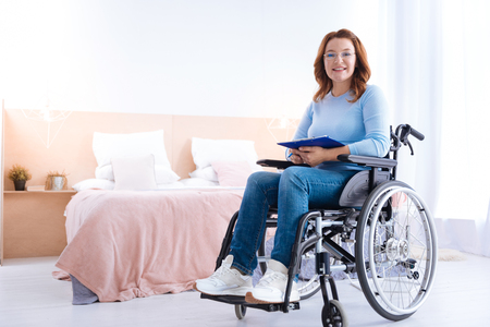 Smiling blond handicapped woman of middle age wearing glasses and holding a pen and a sheet of paper while sitting in a wheelchair in a blue sweater Stock Photo