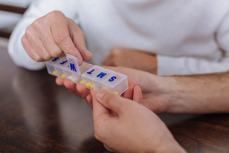 Pill box. Progressive smart pensioner using a special convenient pill box while recovering at home Stock Photo