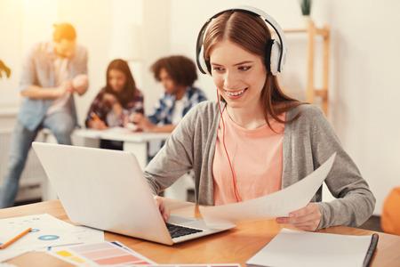 Lass uns das Prüfen. Neugieriger fleißiger enthusiastischer Student, der die notwendigen Informationen im Internet beim Halten eines Dokuments in ihrer linken Hand überprüft