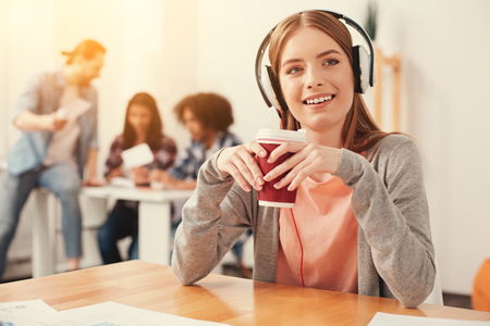 Coffee break. Cute smiling dreamy student having rest and drinking hot coffee while listening to music in her headphones