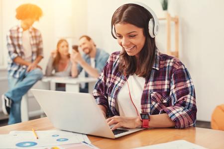 Tipeo rápido Joven entusiasta enérgica mirando la pantalla de su computadora portátil mientras escribe un mensaje con sus compañeros en el fondo Foto de archivo - 89334280