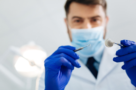Curing teeth. Close up of professional dentist with a mask on his face while holding instruments and standing in front of you