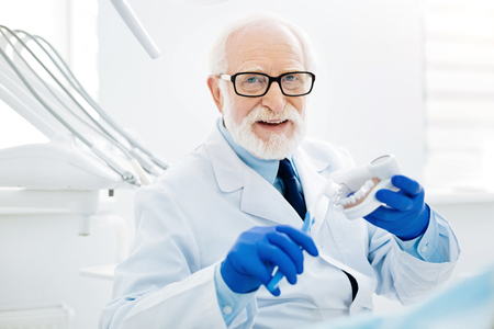 Reminding about healthcare. Close up of optimistic dentist with glasses holding false teeth and tooth brush while looking at you with a smile