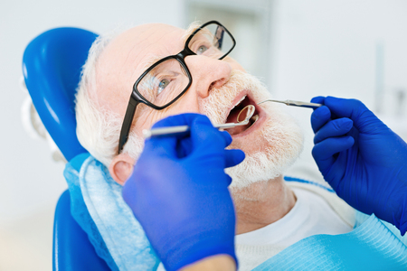 Zorgen voor gezondheid. Sluit omhoog van kalme geduldige zitting op de tandstoel terwijl bekwame stomatologist gebruikend instrumenten en genezend zijn tanden Stockfoto