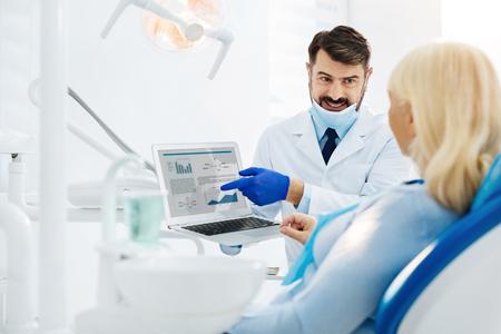 Bruikbare informatie. Positieve ervaren tandarts die laptop in handen houdt terwijl het raadplegen van de patiënt en het hebben van positieve stemming