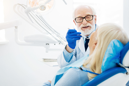 Real professional. Skilled dentist using specific tools and inspecting patients mouth cavity while the patient sitting on the dental chair Stock Photo