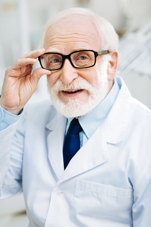 Wise glance. Close up of positive bearded doctor touching his glasses while looking at you and expressing optimism Stock Photo