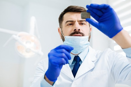 Investigation. Close up of attentive skilled dentist looking at the Xray image while standing in the office