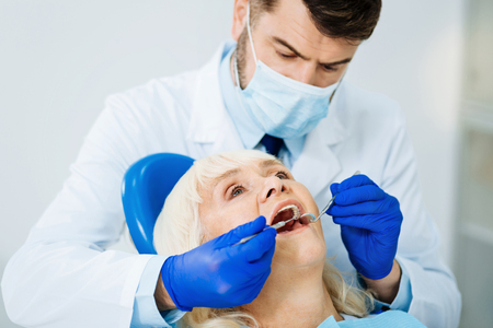 Working process. Close up of skilled diligent dental surgeon using specific equipment while curing the patient Stock Photo