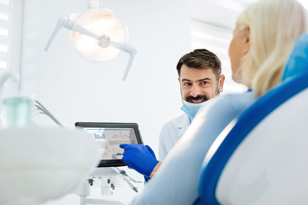 Sounds exciting. Optimistic stomatologist with a dental mask on his face using a tablet while consulting the patient