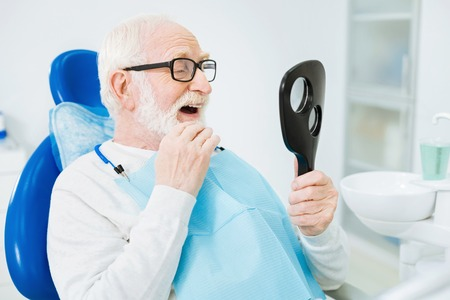 Admiration. Close up of concentrated bearded man looking in the mouth mirror while touching his chin and being concentrated