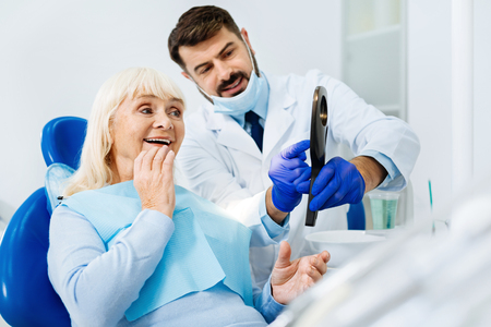 Pleased with result. Smiling woman expressing cheer while looking in the dental mirror and admiring her healthy teeth Stock Photo - 89709576