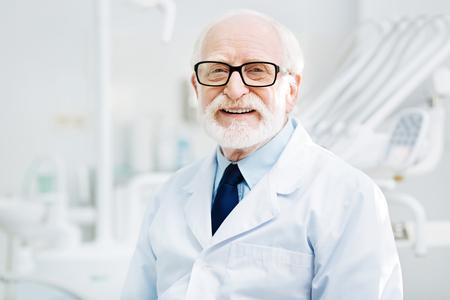 私の仕事の自慢しています。陽気な感情を表現しながら笑みを浮かべてあなたに楽観的な経験豊富な医師のクローズ アップ