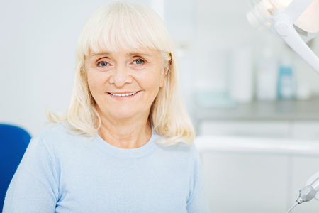 Caring about teeth. Close up of cheerful woman expressing satisfaction while sitting on dental chair and smiling at you Stock Photo