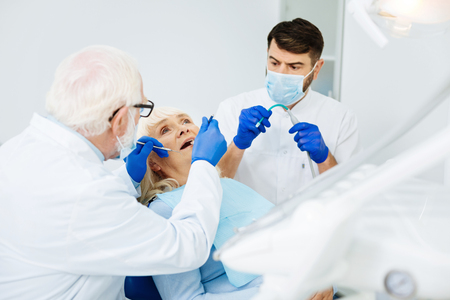 Hard work. Experienced dentist using specific tools while his colleague helping him in the process of curing patients teeth