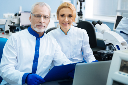 Smiling happy grey-haired scientist wearing glasses and a pretty blond young woman wearing a uniform and equipment in the background