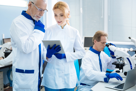 Grey-haired wrinkled researcher discussing results with a beautiful blond young scientist while being in the lab and another researcher working with a microscope in the background