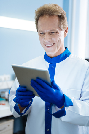 Handsome happy smiling biologist holding a tablet and wearing a uniform while being in the lab