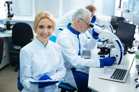 Attractive content blond young researcher smiling and wearing a uniform while other serious researchers working with a microscopes in the background Stock Photo