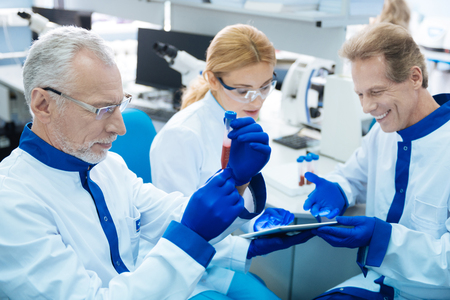 Serious grey-haired experienced researcher holding and looking at the test tube while two others looking at the tablet in the background