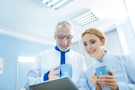 Vigorous smiling grey-haired bearded scientist and content female blond researcher holding cups and looking at the screen while being in the lab