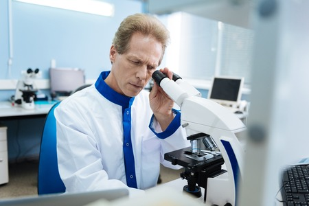 Attractive serious researcher of middle age wearing a uniform and looking into a microscope while making an analysis Stock Photo