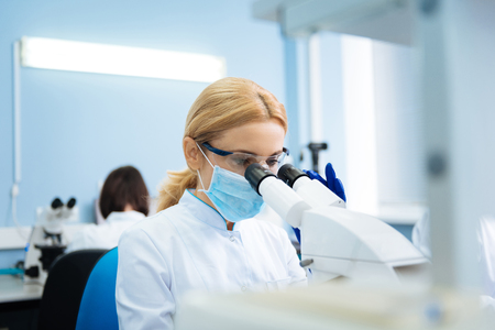 Concentrated blond young researcher wearing a uniform and a medical face mask and gloves and glasses and looking in the microscope while being in the lab