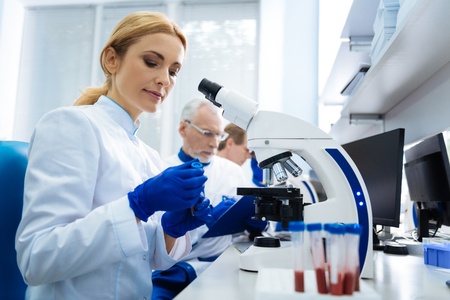 Concentrated blond young researcher sitting at a microscope and holding test tubes while wearing a uniform in the lab and two other researchers working in the background