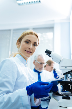 Vigorous blond young researcher sitting at a microscope and wearing a uniform in the lab and two other researchers working in the background Stock Photo