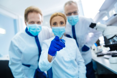 Cheerful vigorous experienced researchers wearing a uniform and a medical face mask and gloves and glasses and the female scientist sitting Stock Photo