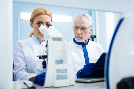Concentrated grey-haired bearded old scientist holding a tablet and looking at a blond young researcher sitting next to him and working with a microscope in the lab