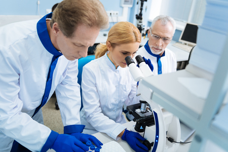 Concentrated grey-haired bearded old scientist holding a tablet and looking at a blond young researcher sitting next to him and working with a microscope