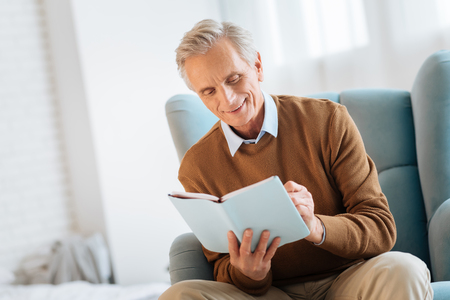 Positive minded elderly man smiling cheerfully while writing something down in his notebook at home.