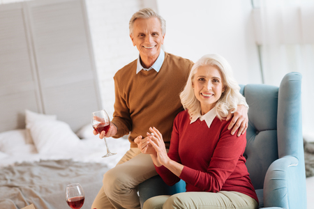 Harmonious elderly husband and wife looking into the camera with cheerful smiles on their face while sitting in a chair and enjoying the glasses of red wine.