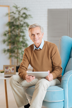 Happy retired man relaxing in a chair and looking into the camera with his eyes full of joy while using his tablet at home.