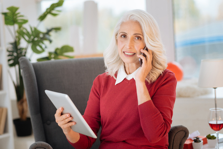 Beautiful retired woman listening to her friend talking on phone while sitting in a chair and working on a tablet computer at home. Stock Photo