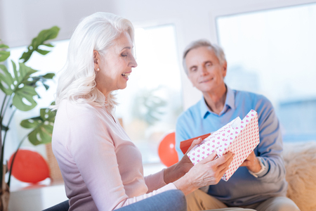 Side view on an excited elderly woman sitting next to her husband and smiling while looking at her gift.