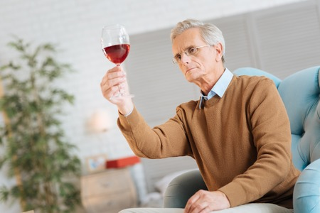 Low angle shot of a serious elderly man sitting in a chair and concentrating on a glass of red wine while examining it at home.