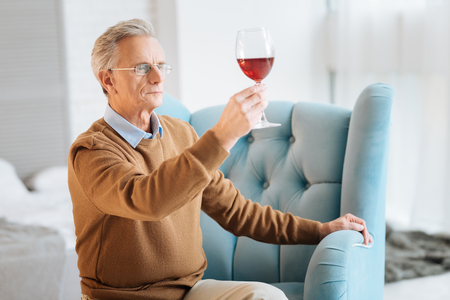Focused retired gentleman in glasses lifting his hand with a glass of red wine while looking at it and analyzing.