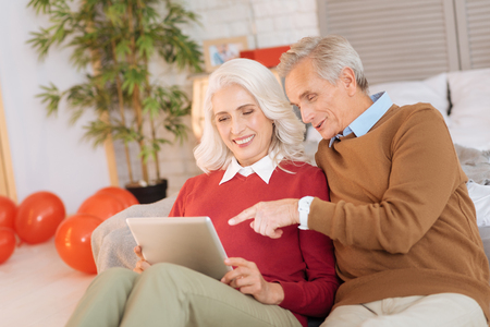 Positive minded husband and wife smiling while discussing something on a digital table emotionally. Stock Photo