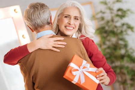 Extremely happy senior woman getting excited and embracing her husband tightly after receiving a gift from him.