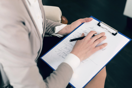 Professional psychologist sitting in her cabinet and holding notes on knees while trying to make decision Stock Photo