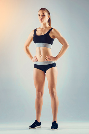 Low angle view on a confident young woman posing with her hands on the hips while standing on feet shoulder width apart. Stock Photo
