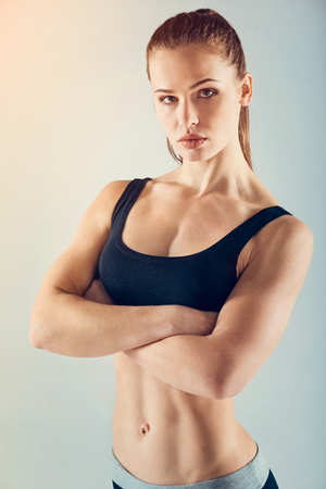 Beautiful sportswoman wearing a navy blue sport clothing posing with her arms crossed and looking into the camera confidently.