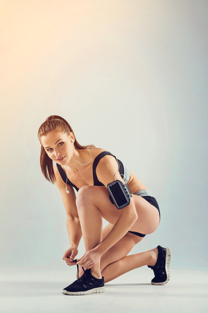 Female athlete of unearthly beauty with earphones looking into the camera while standing on one knee and lacing her running shoes.