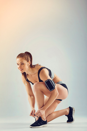 Positive minded sportswoman standing on a knee and looking ahead while tying laces for jogging.